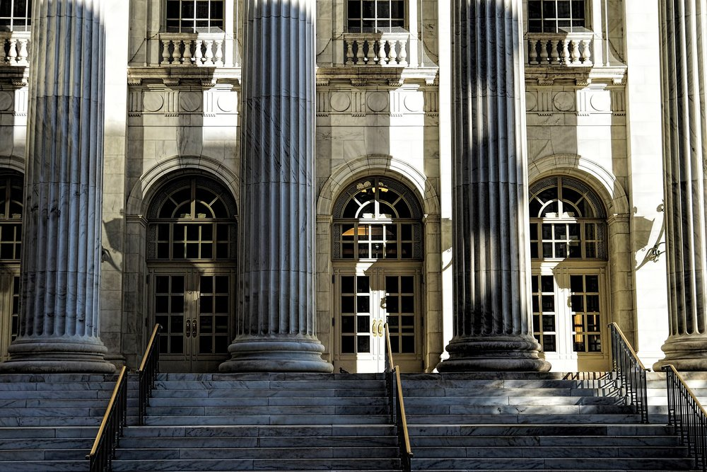 Photograph: Beautiful old courthouse doors and steps bathed in late afternoon sunlight.