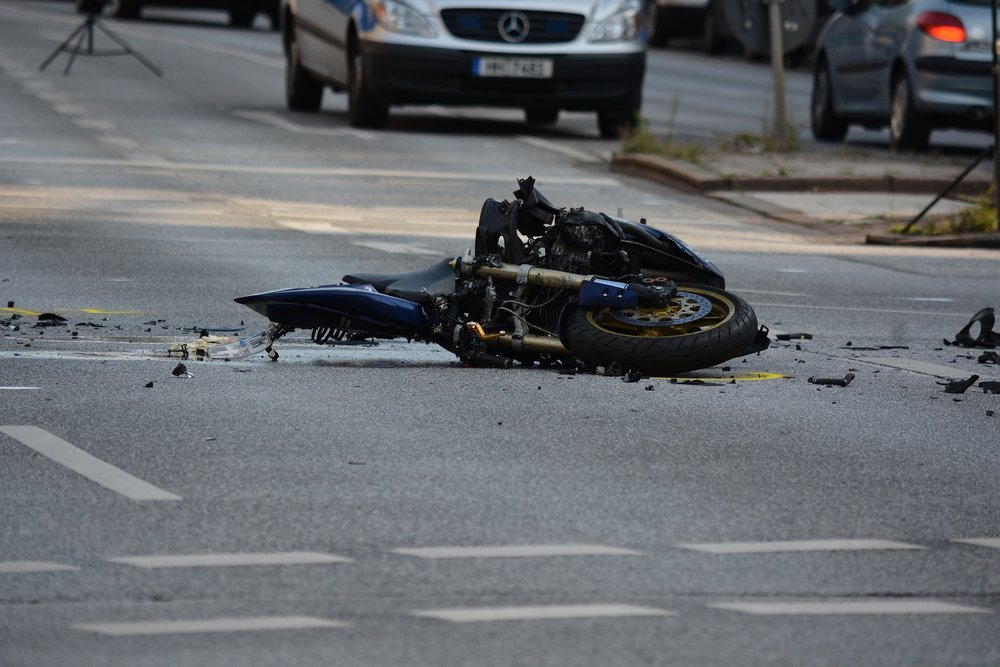 Photograph: Wrecked motorcycle lying in the street having been hit by a car.