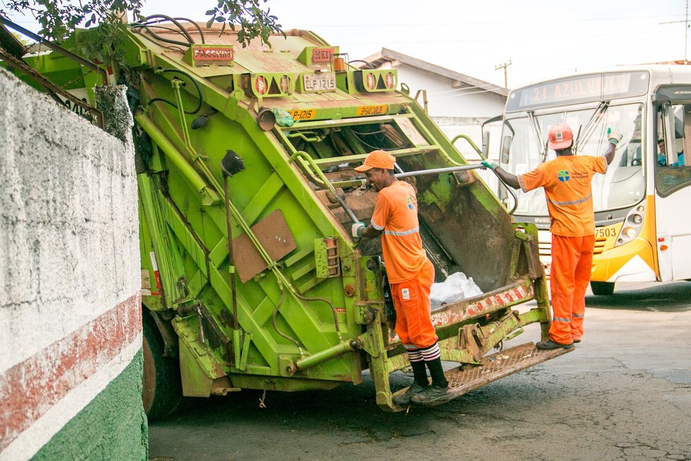 Photograph: Workers in uniform riding on the back end of an open garbage truck.