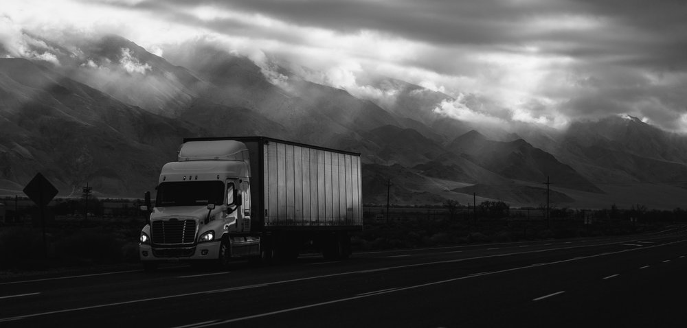Photograph: Semi-tractor and trailer on a cold open road with mountains and dark clouds.