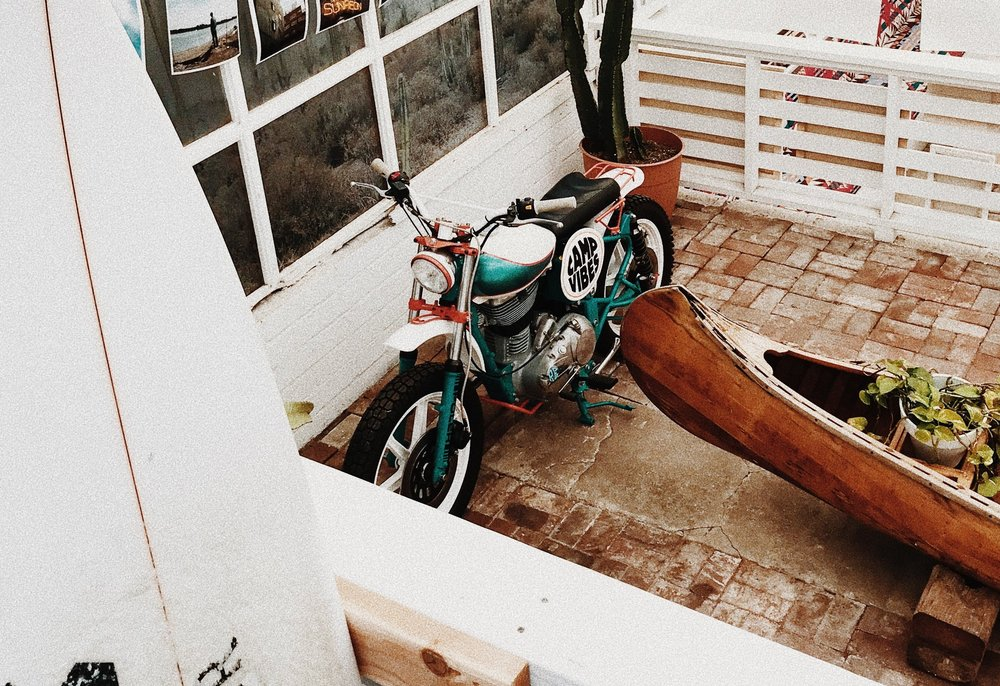 Photograph: Motorcycle parked in an enclosed porch.