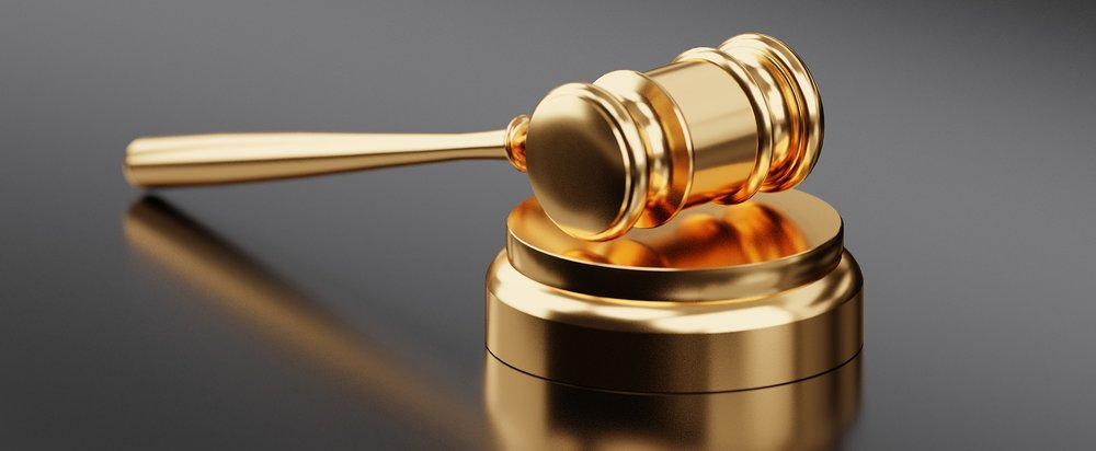 Photograph: a golden law gavel resting on its base.