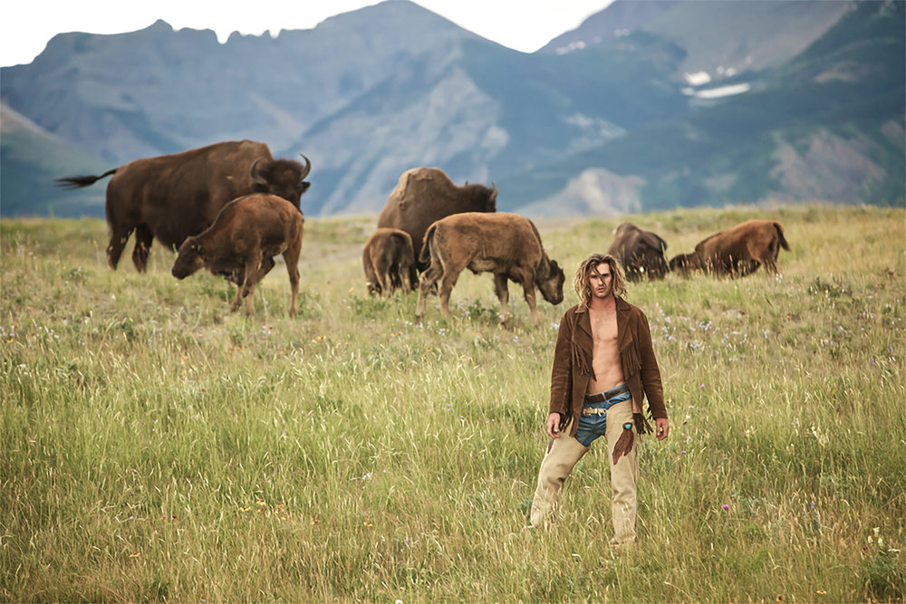 Callum Snell  among wild Buffalo wearing Buffalo Girl custom made chaps, jacket, and belt.