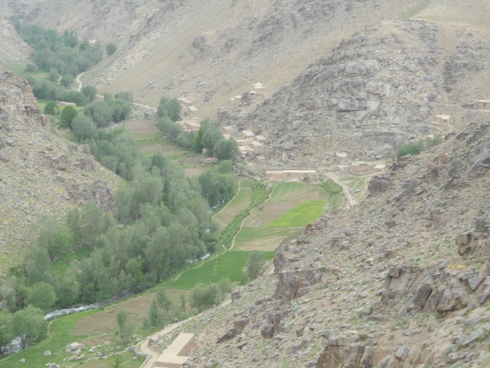 Naik village in summer. The valley to Khak Khuday Dad begins behind the rocky ridge on the left. The L-shaped house in the foreground was Naimatullah's father's. The long house in the centre of the picture was Abdullah Kalta's. Their families have rebuilt the houses.