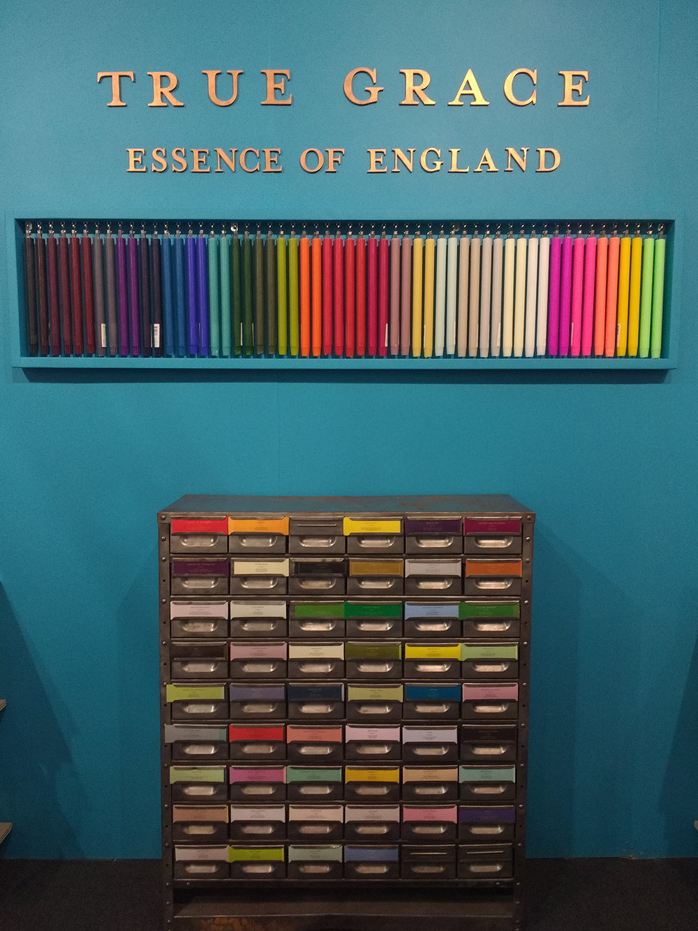 Collection of coloured candleswith drawers stocking scent sample packs.