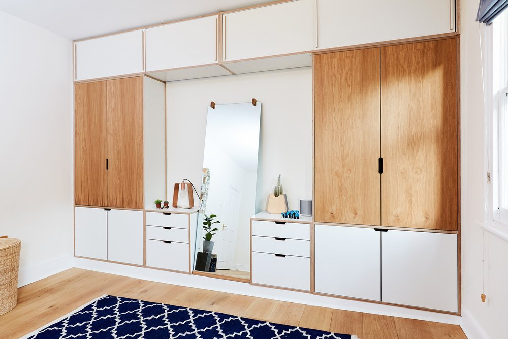 The elegant wall of fitted wardrobes in the bedroom. Cass needed some easy to access but hidden storage as well as a full length mirror but didn't need extensive hanging space, so Soroush designed a practical wardrobe for her. The sliding cupboards at the top can be stuffed full of winter bedding and towels without popping open and the open space around the mirror extends the room to its full depth. Lozi offers a full range of made to measure  fitted wardrobes .
