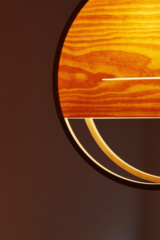 Detail of Lozi's Sunset Lamp's pine veener texture and warm orange glow