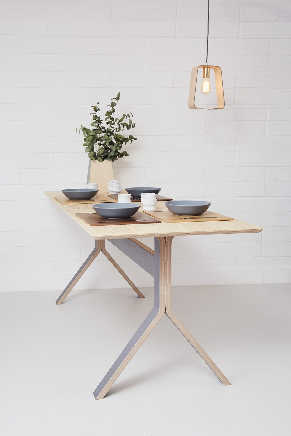 Lozi's minimal plywood Sea table, used as a dining table.