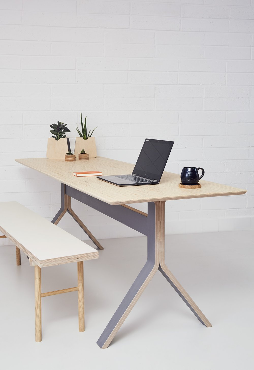 Lozi's minimal plywood Sea table, used as a co working desk space
