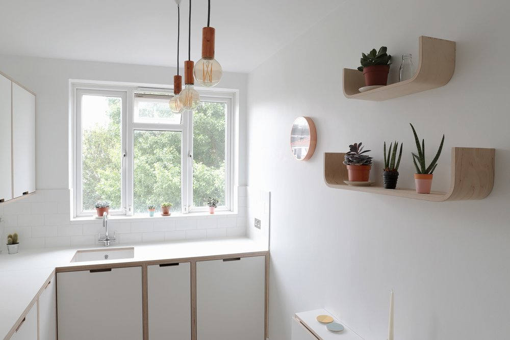Free hanging U shelves allow the couple to display plants and small decorative items.