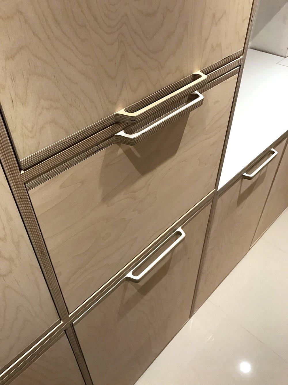 The elegant curved handle detail seen across the kitchen with a close up of the patterns seen in birch plywood veneer.