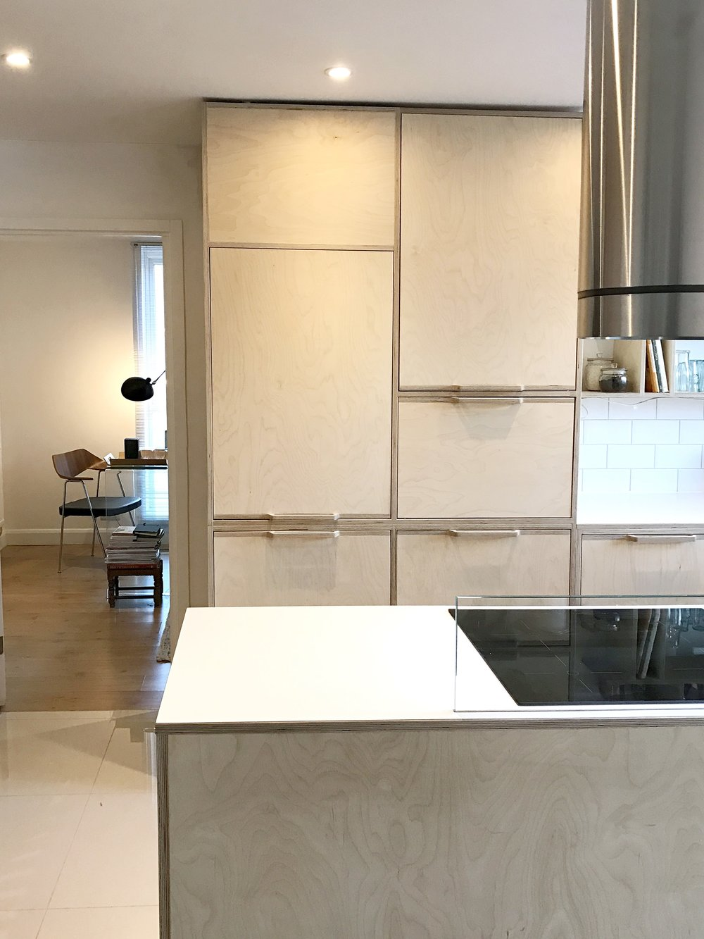 A closer view of the fridge cover and the tall kitchen cabinets, with a sneak peek into the couple's elegant living room.