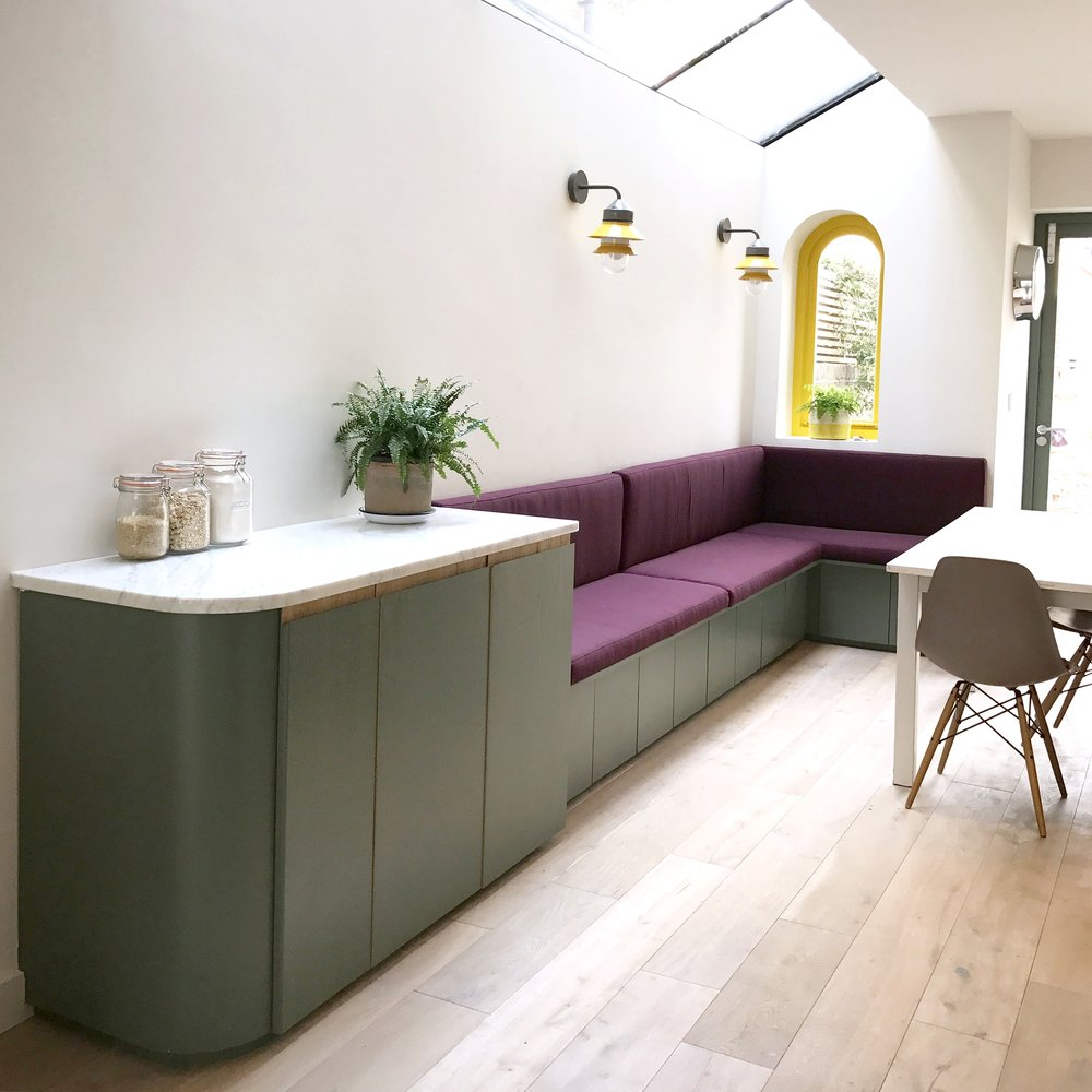 The deep purple seating and dining area, with ample hidden storage.