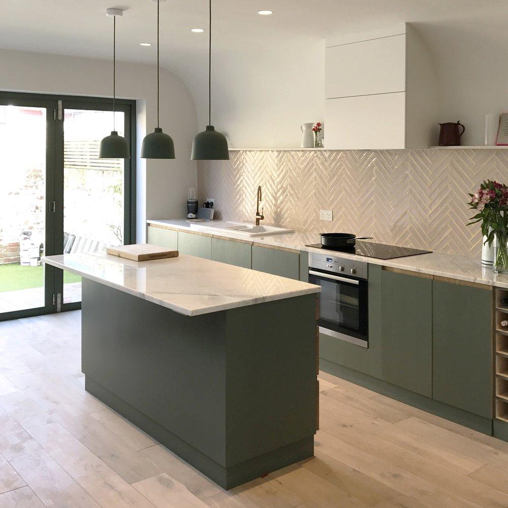 The full kitchen and island, with marble worksurface and herringbone tile backsplash.