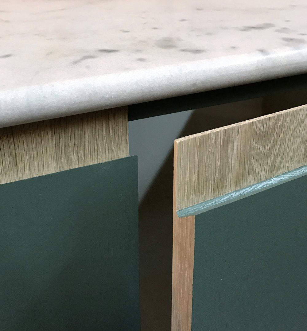 The solid oak doors with soft close hinges nestled under a marble worksurface.