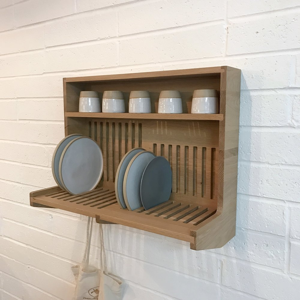A solid oak wall mounted shelving system that also doubles as a draining board.