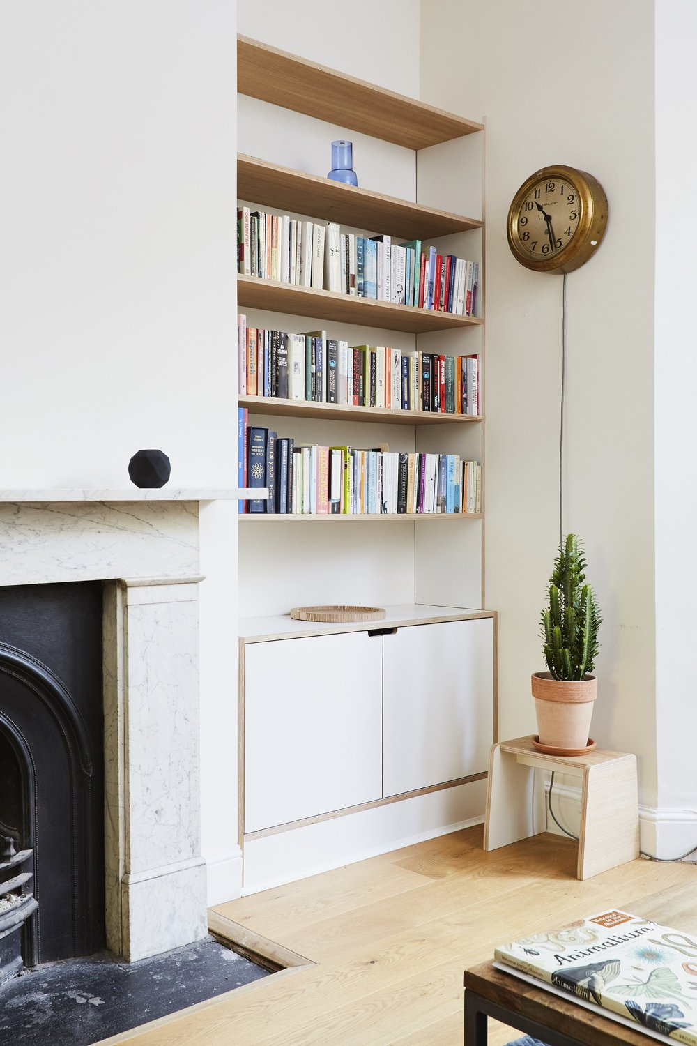 The plywood bookshelves nestle neatly within the alcoves either side of the fireplace. Lozi wanted to create practical storage without distracting from the beauty of the original features.