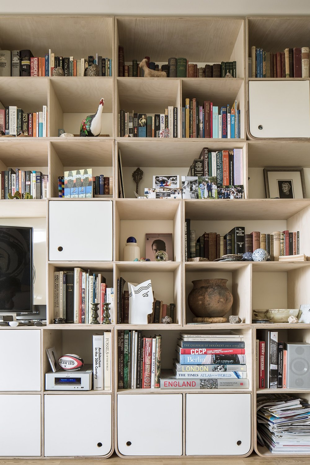 The varying sizes of the alcoves give the bookshelf a rhythm, creating an interesting and irregular shape.