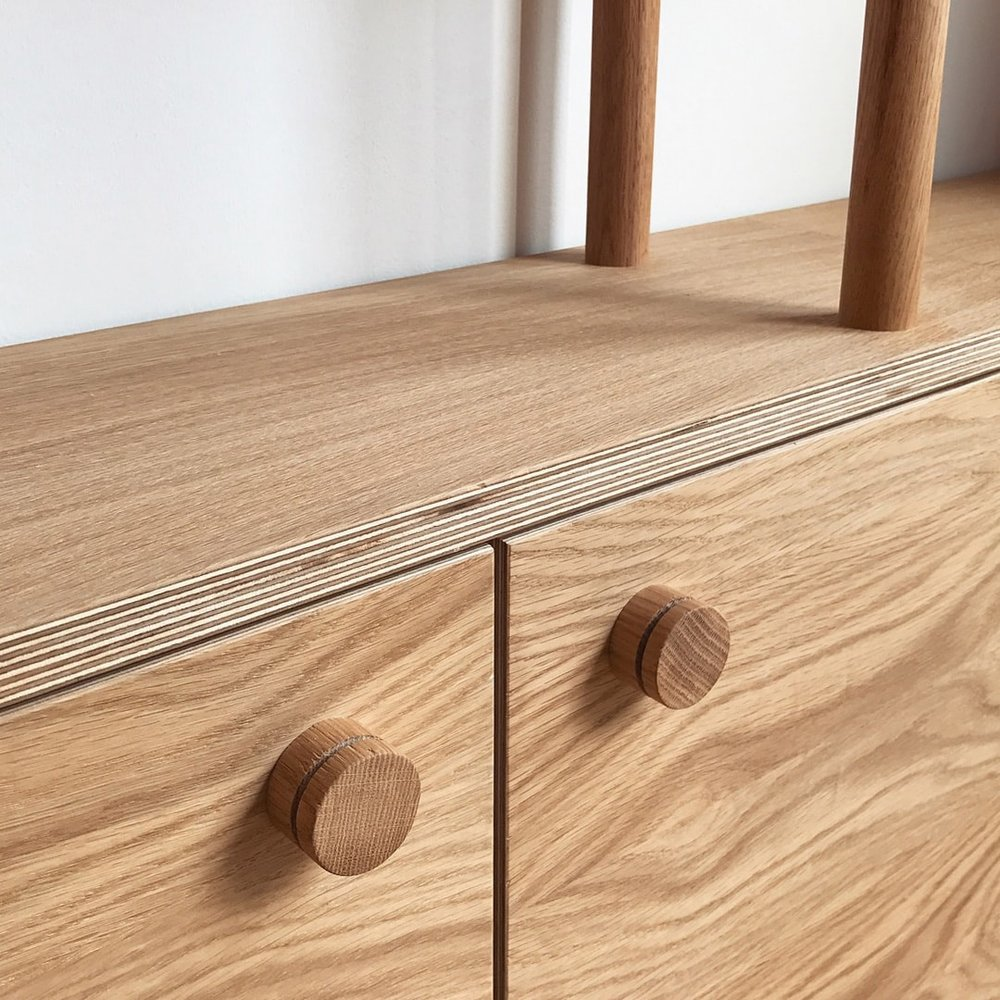 A close up detail of the oak dowel handles on the lower cupboards.