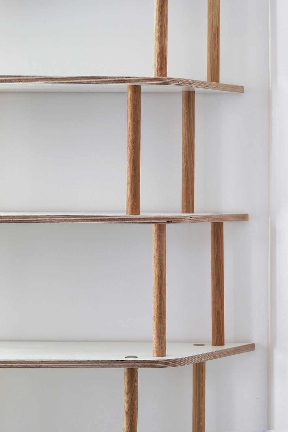 The edge of the open plan shelving is angled to mirror the angle of the room. Solid oak dowel legs, offset to create a design focus, support the shelving.