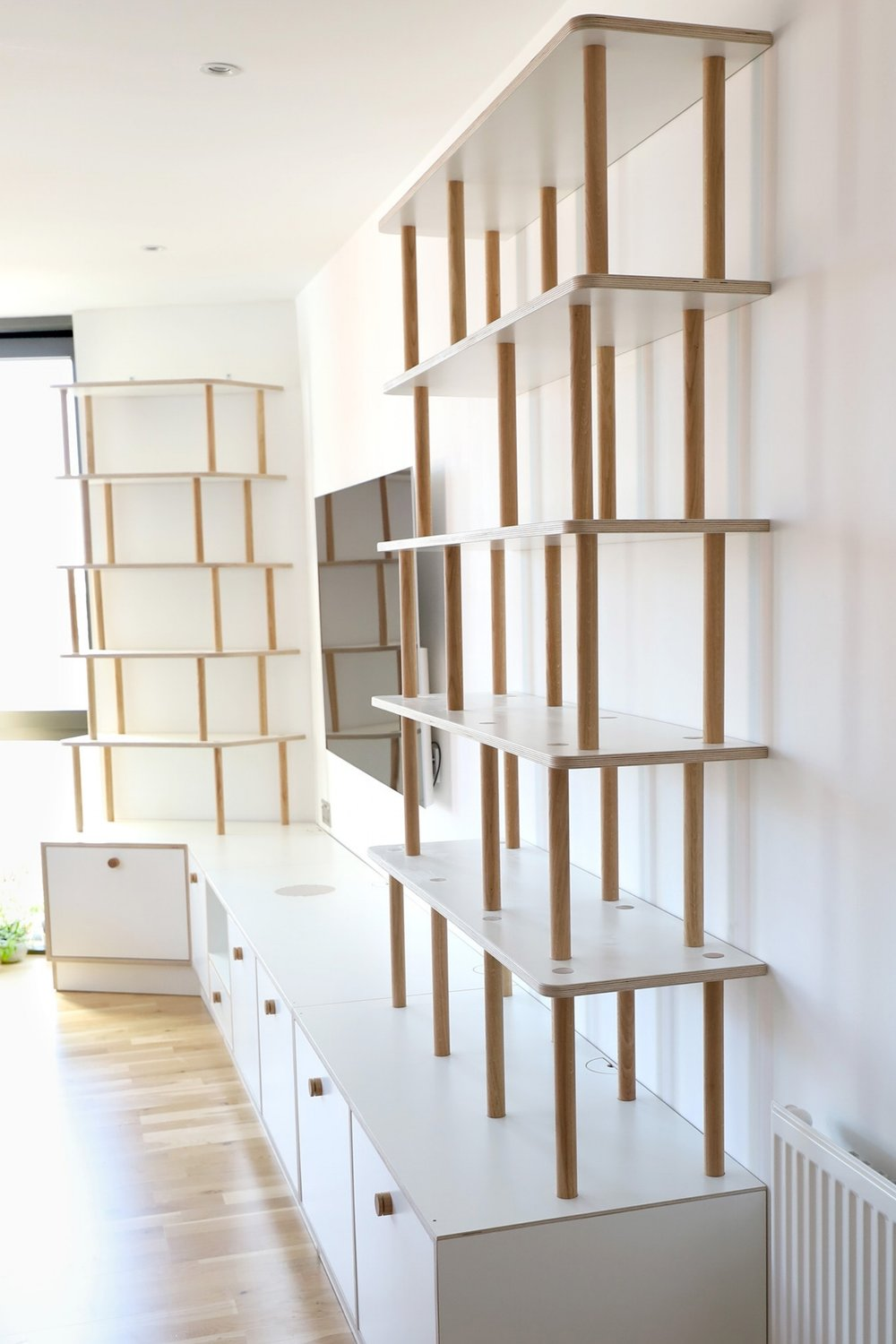 The shelving system is made to fit perfectly into the wide angled corner of the room.