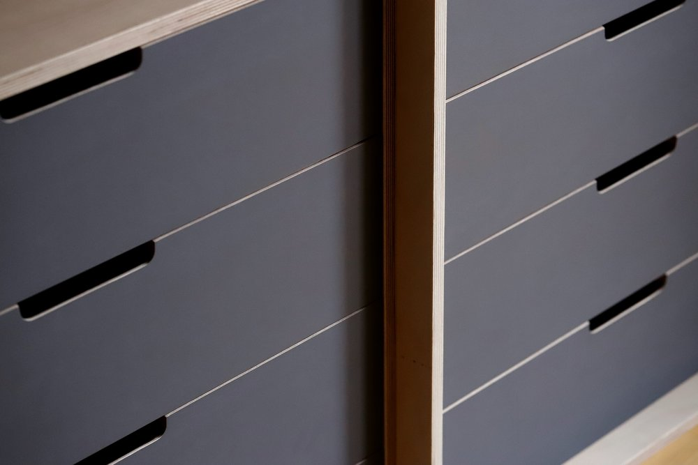 The dark grey drawers help elongate the space.