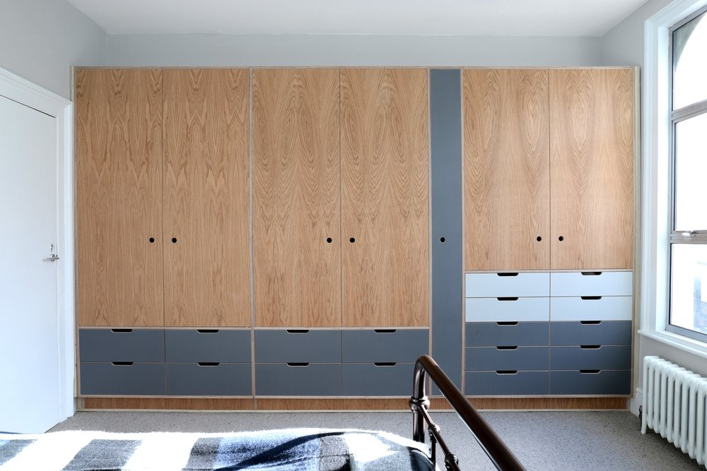 Robin's large fitted bespoke wardrobe, made from oak and plywood by Lozi, in East London
