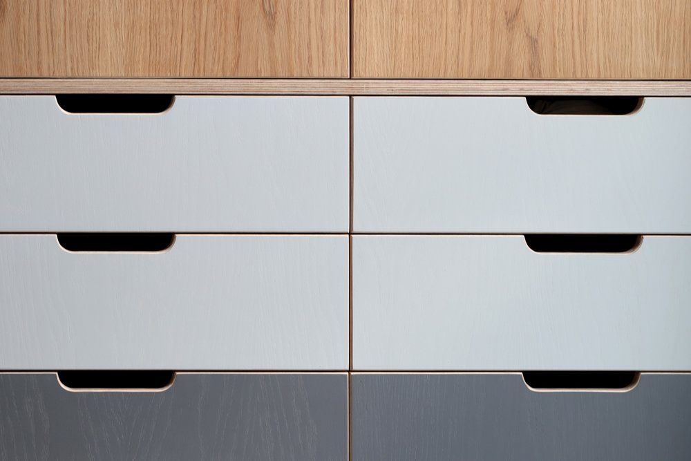 Handle detail of Robin's large fitted bespoke wardrobe, made from oak and plywood by Lozi, in East London
