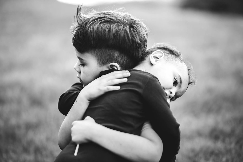 big brother and little brother hugging outdoors in candid photo