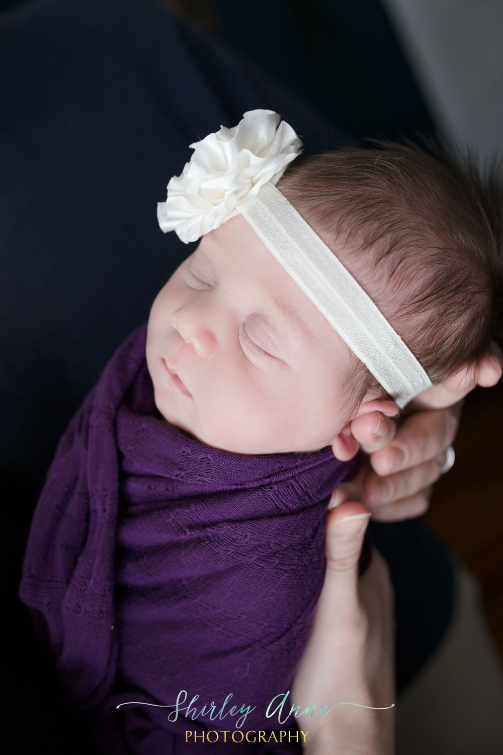 newborn baby girl held by mom wrapped with headband.