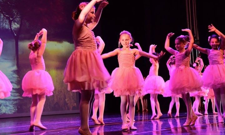 A cut-out image of girls who are about 8 years old onstage. They are in pink, lit blue and purple. In the middle of the frame a small blonde girl dominates the image, her arms in motion, a smile on her face.