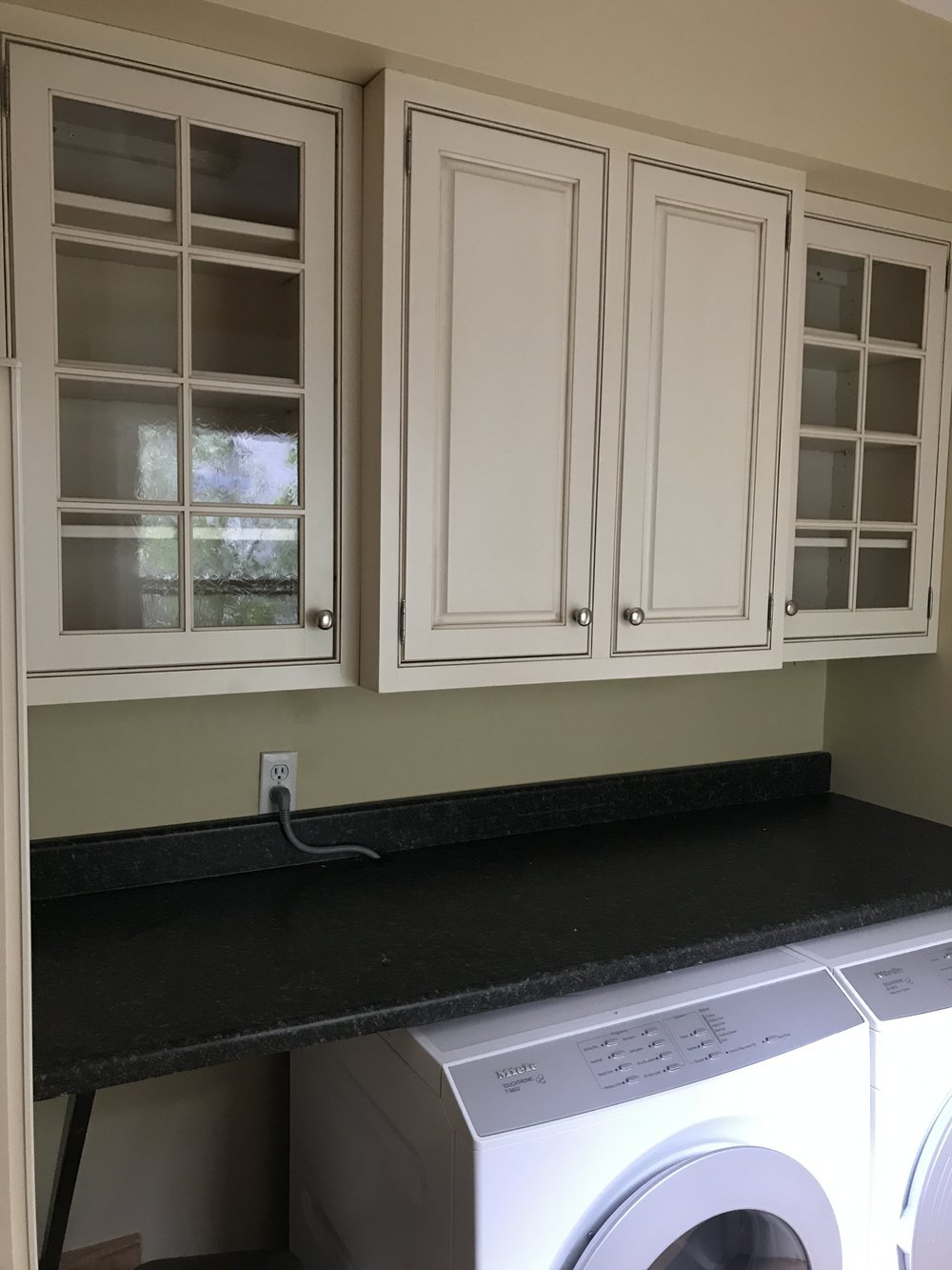 - here over my washer and dryer. They look so much better than the old laminate cabinets we removed! Once the big renovation is done, I'll focus on the laundry room and probably paint these a fun color.*Note that this area is going to be my make shift kitchen during the renovation