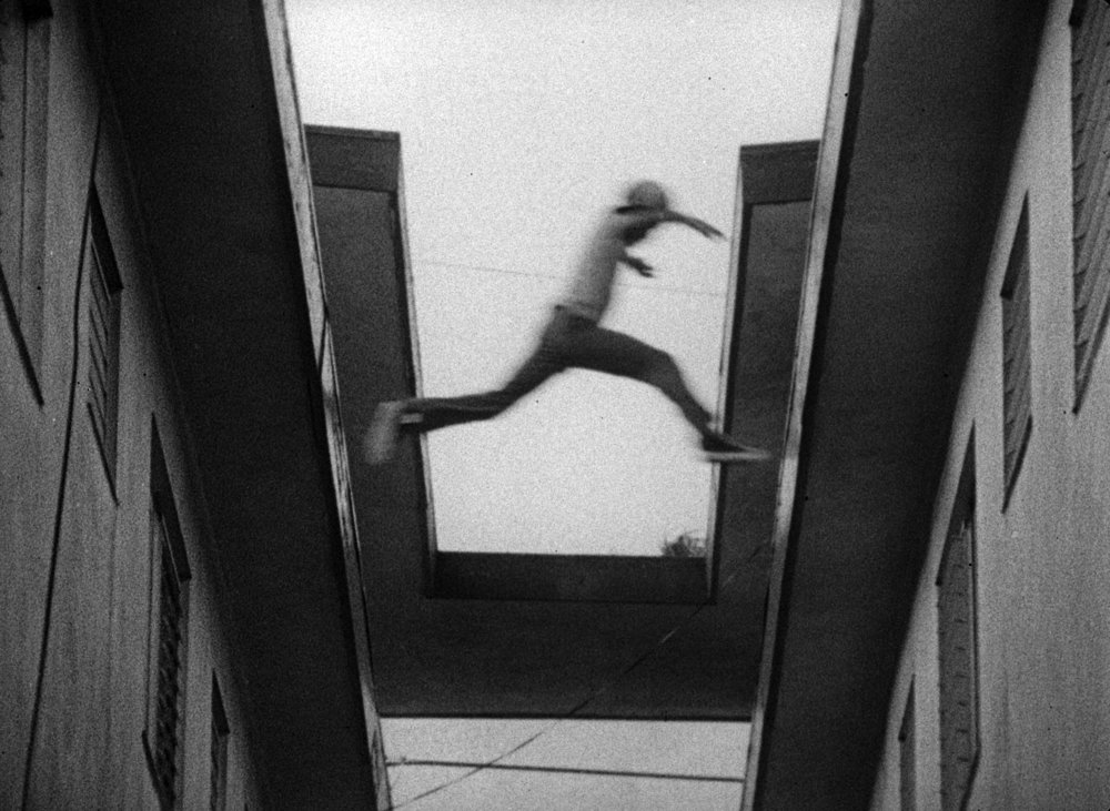 """Every time I see it,"" Charles Burnett says of this image, ""I cringe.""  When filming  Killer of Sheep , Burnett didn't think of what might have happened had one of the kids who jumped between the buildings didn't make it. ""It's a gap of three or four feet,"" he says in the podcast. ""At the time I was doing it, it never occurred to me what would happen if those kids fell. The fact of the matter is they did it all the time ... but I shouldn't have allowed it to happen."""