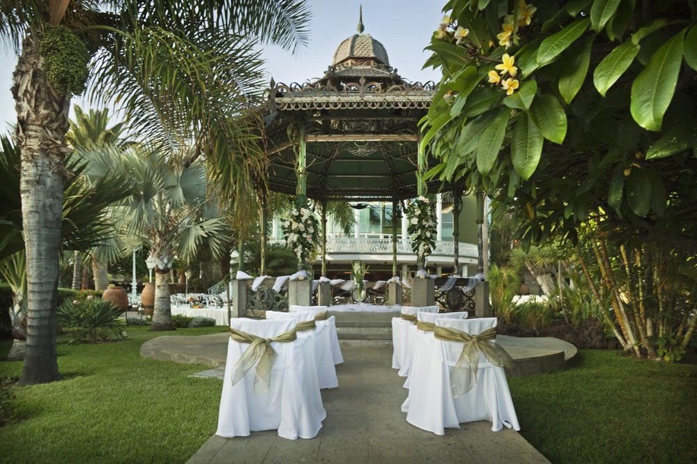 Stunning wedding ceremony gazebo surrounded by palm trees and the river