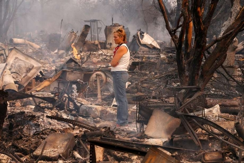A woman stands on the pile of ashes of where her home once stood due to the wine country wildfires