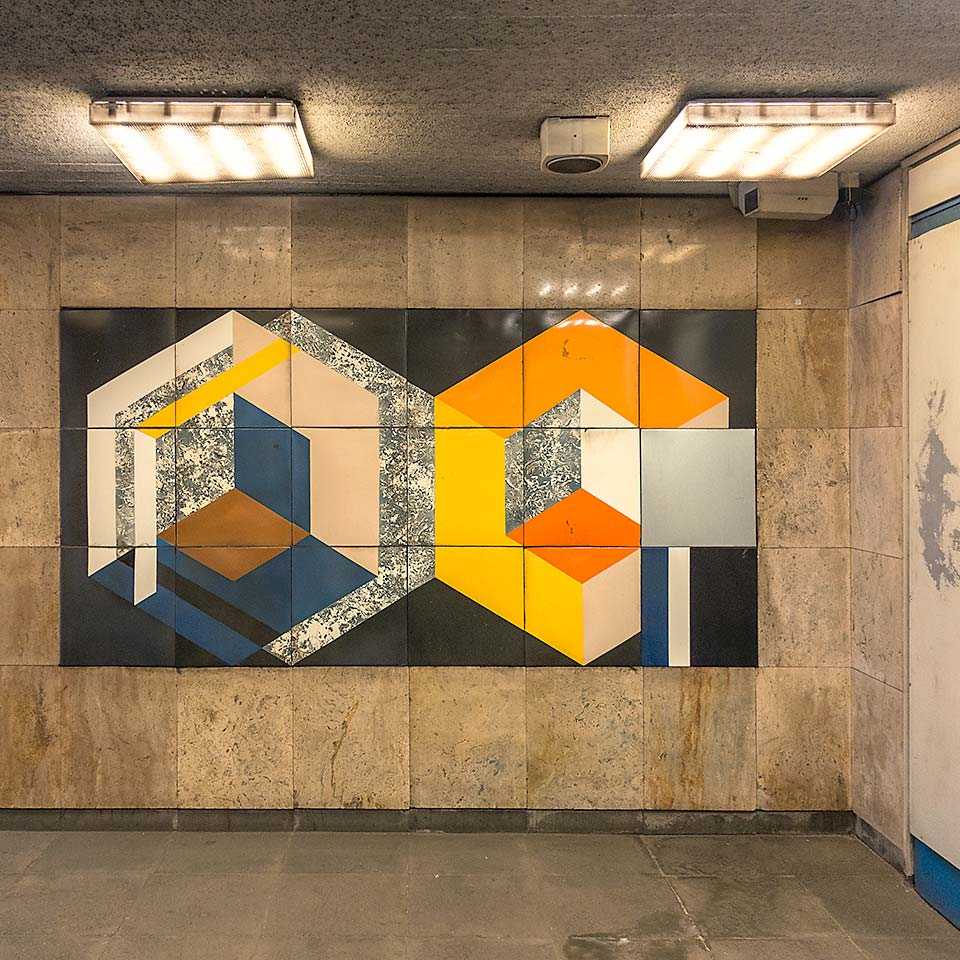 Some late 80s graphic art for the masses at the entrance to the M3 platform at Forgách utca station. One panel is missing and at bottom right is a panel apparently requisitioned from another artwork down the platform which is now mostly missing.