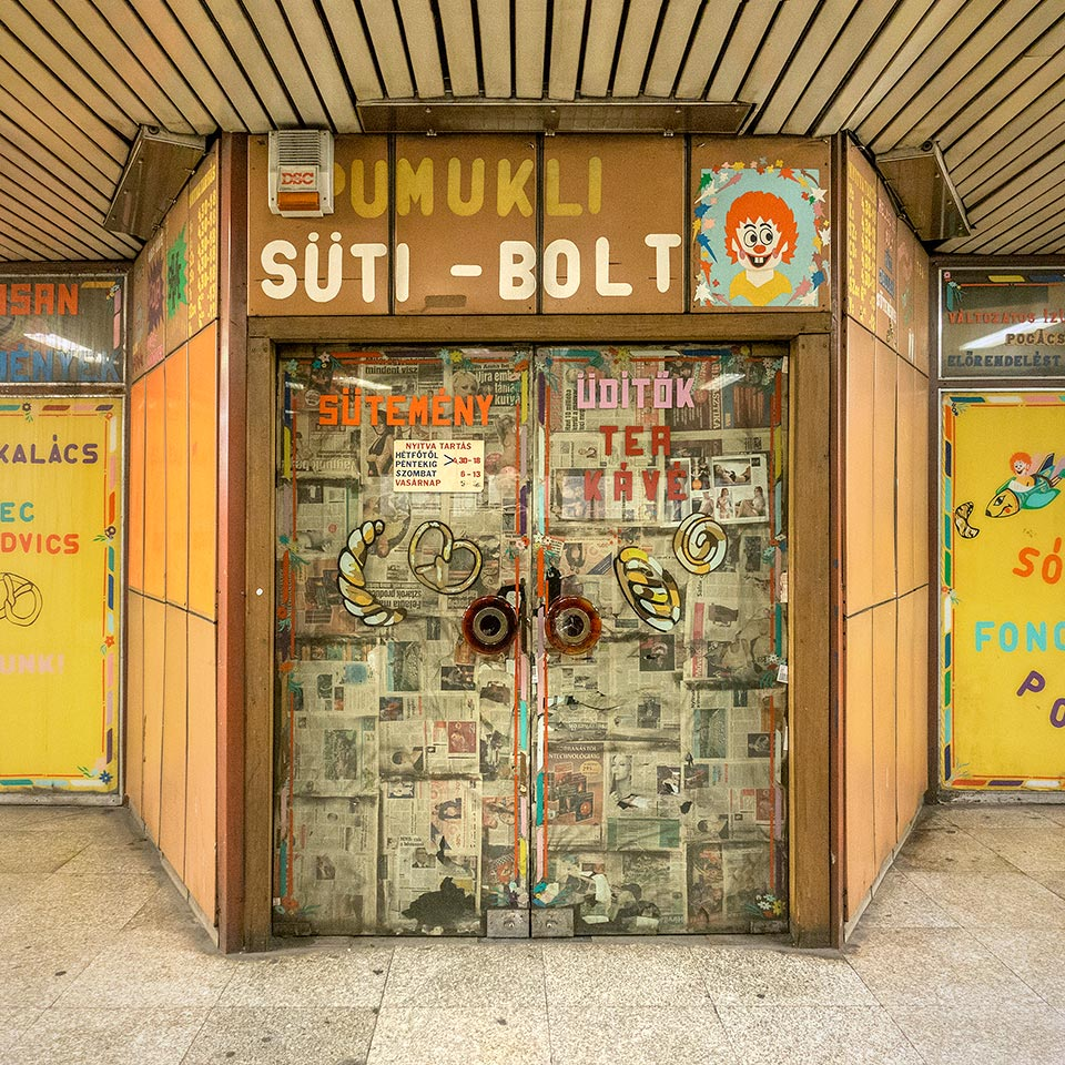 The shuttered Pumukli cake shop in Budapest Metro's 1981 Lehel tér station. Pumukl is the name of a German cartoon character (a clownish sprite only visible to master carpenter Eder) invented in 1961 and popular in Hungary.