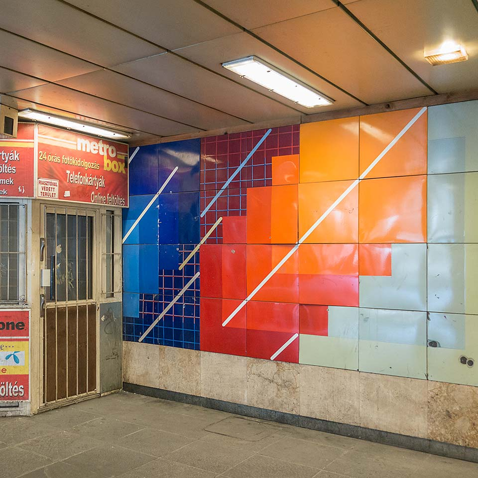This colorful corner in Gyöngyösi utca station on Budapest's M3 line sports some bitchin' 80s supergraphic artwork partially obscured by the more recent kiosk addition.