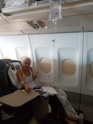 FIT Founder Kelly sitting in a window sit and getting some much-needed fluids during a flight between continents at the 2018 World Marathon Challenge.