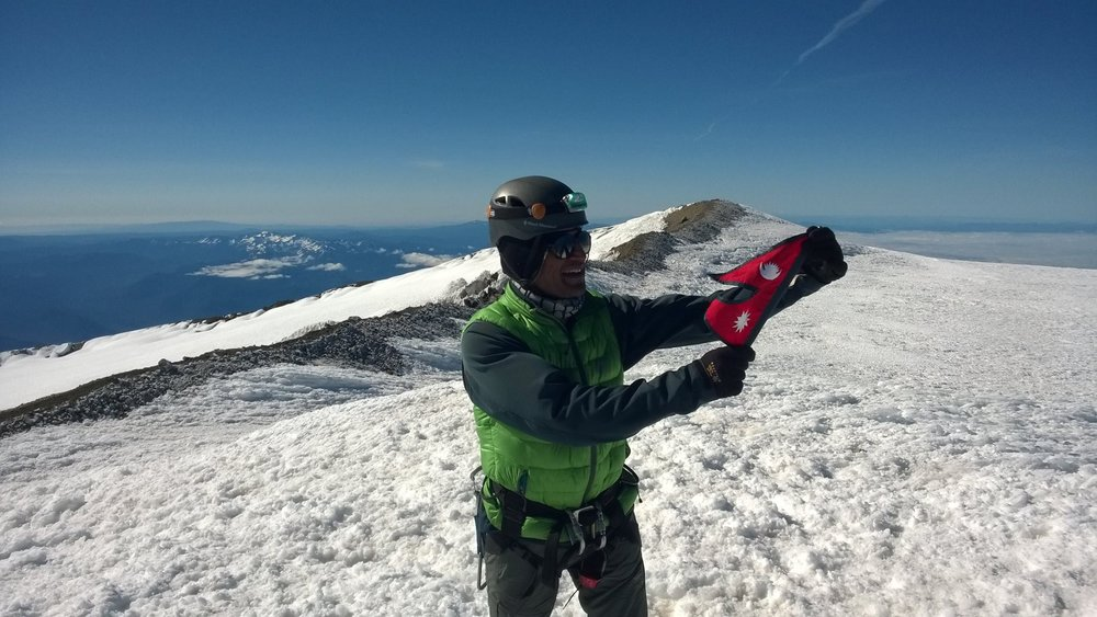 Yogesh Satyal proudly desplays the Nepal flag on the summit of Mt. Rainier