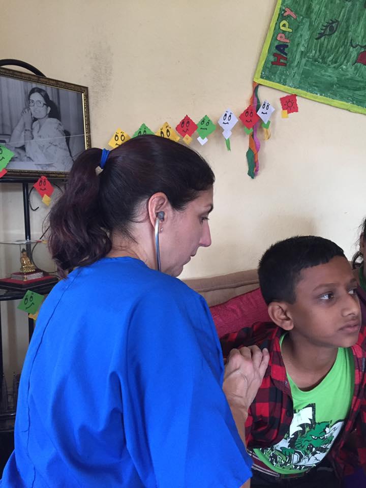 Dr. Donna Thackery, President of Karma Thalo examines a child.