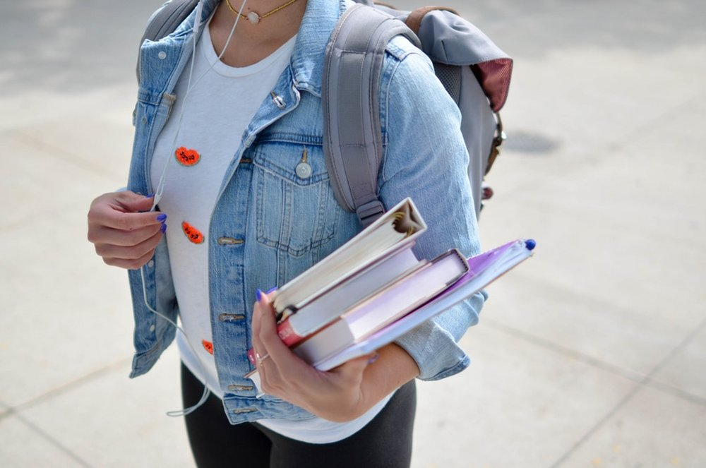 A young student wearing a denim jacket , a backpack and listening to headphones