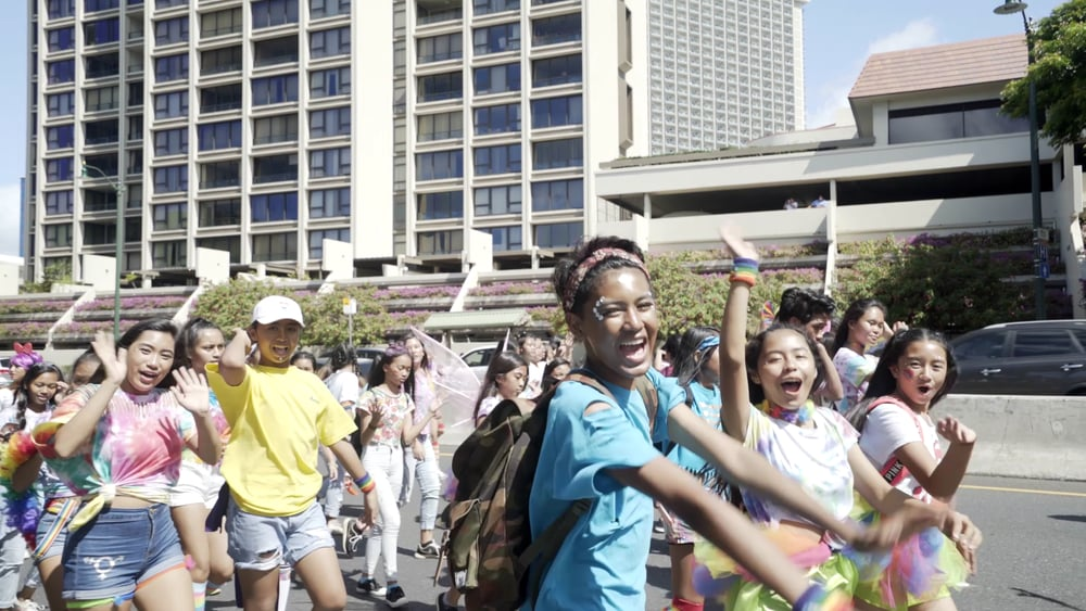 A group of youth walking in the pride parade, they are all waving at the camera, wearing tutus and jewels and tye-dye.