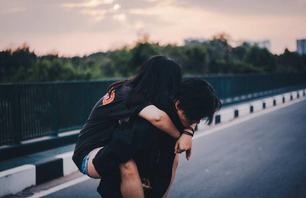 One teen giving another teen a piggy back ride on a bridge.