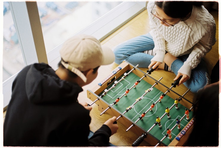 two individuals sitting on the ground playing foosball