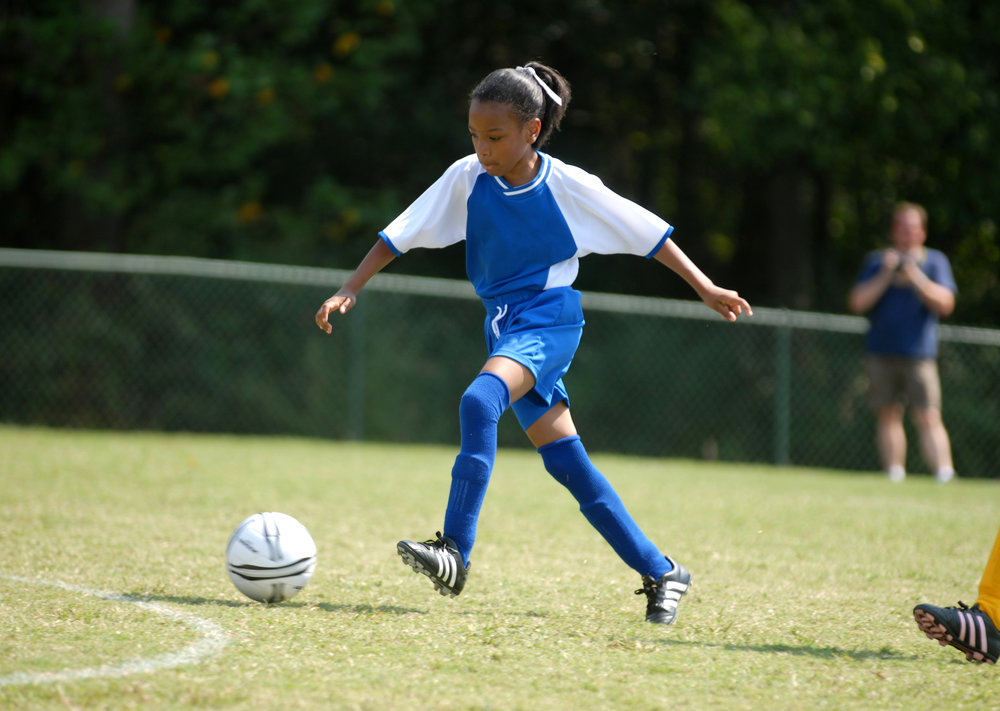 african american girl playing soccer with determination