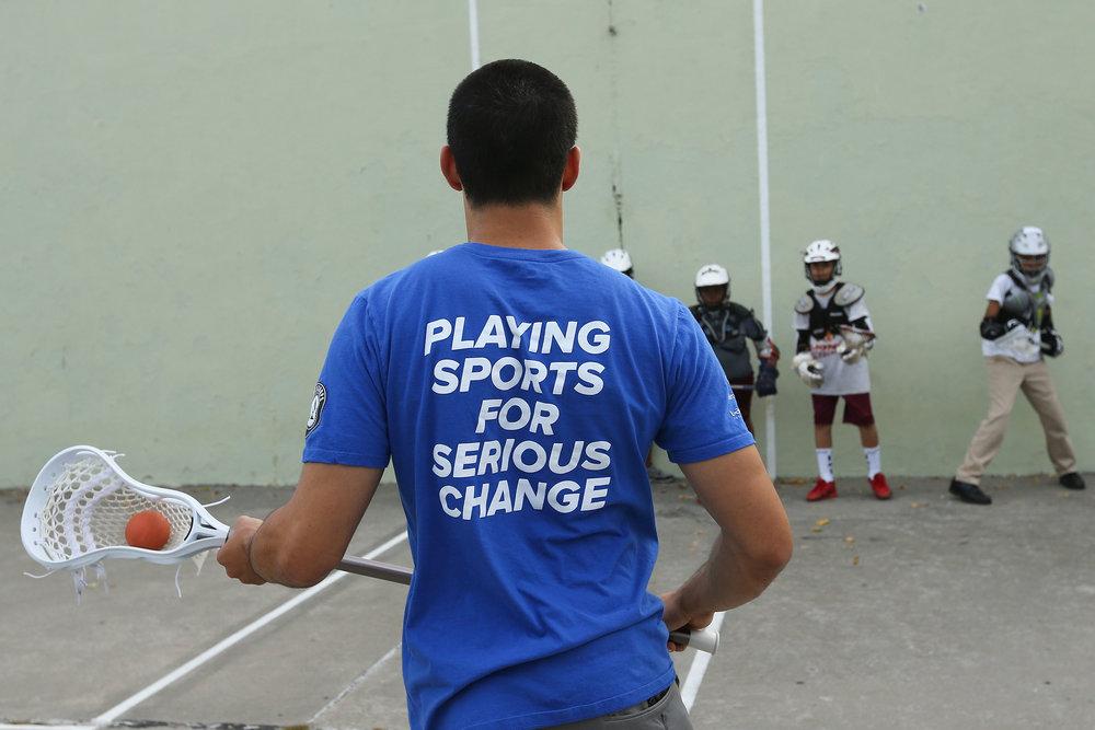 Harlem-Lacrosse-Coach-with-Boys-Team.jpg