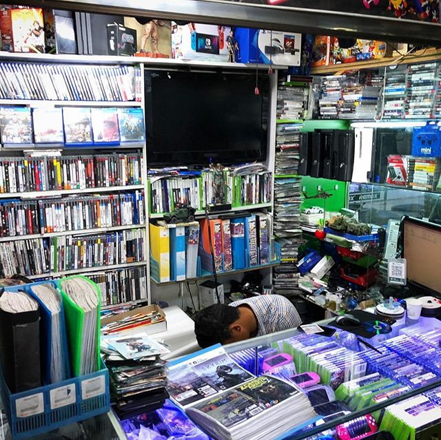 Our last stop of the trip showed how most players in Mongolia (and many around the world) acquire their video games: a black market game shop. Customers browse a binder of photocopied PC game covers (bottom left) and pick which game they would like burned to disc. Each disc costs 2500 MNT (about 1 USD) and takes about five minutes to burn. The shop sells legitimate console games too (used and new), but these are relatively expensive since they are priced near MSRP. The owner of this shop was very nice and allowed me to take this picture, but deliberately hid his face. More behind-the-scenes at 🗺 patreon.com/clothmap . #whatareyabuyin #clothmapping #behindthescenes #travelstories #mongolia #ulaanbaatar #travelasia #asiatravel #blackmarket #piratedgames