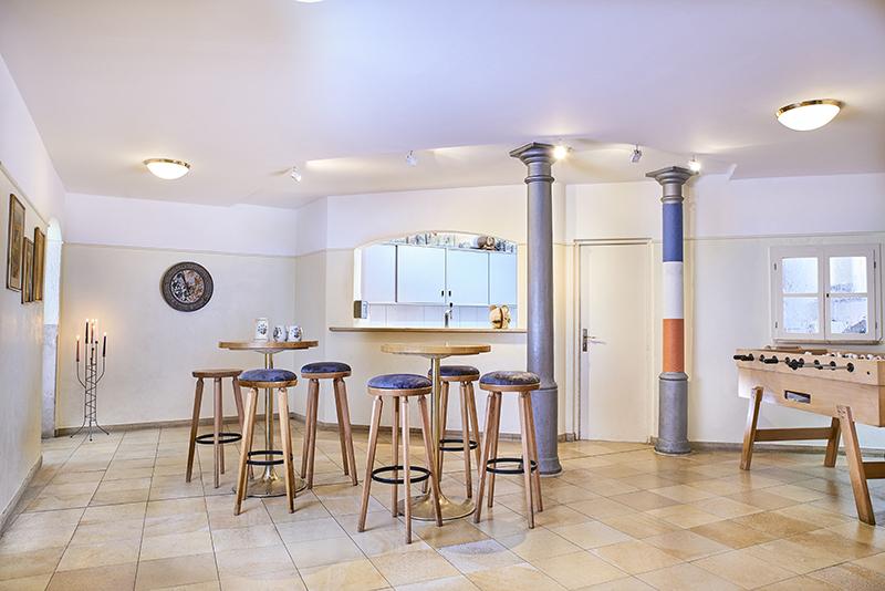 Foyer - Das Foyer bildet den zentralen Punkt in unseren Verbindungsräumlichkeiten. Egal ob zum Kickern, Kartenspielen oder einfach zum Zusammensitzen, dank seiner zahlreichen Sitz- und Stehmöglichkeiten lädt es zu gemütlichen Abenden mit Freunden ein. Es verfügt über eine separate Garderobe sowie einen professionellen Barbereich. Durch einen Exklusivvertrag mit der Münchner Brauerei Augustiner werden wir wöchentlich mit Getränken wie Bier, Limonade, Spezi oder Wasser versorgt, sodass keiner dursten muss.