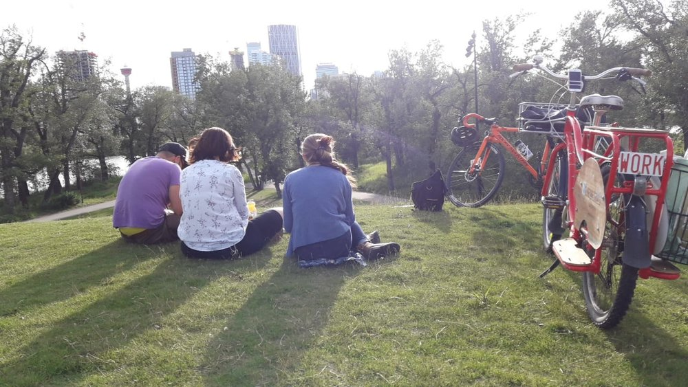 A few riders enjoying a sunny view of the city from their park stop on St. Patrick's Island